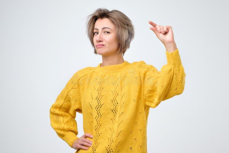 Vrouw die kleine hoeveelheid iets met vingers tonen stock afbeelding