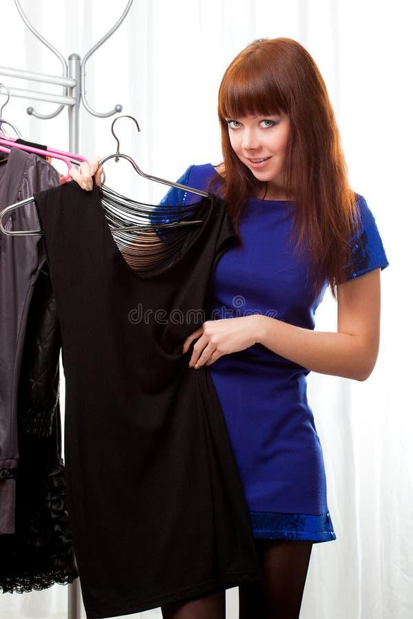 Vrouw die kleren vindt bij opslag stock foto