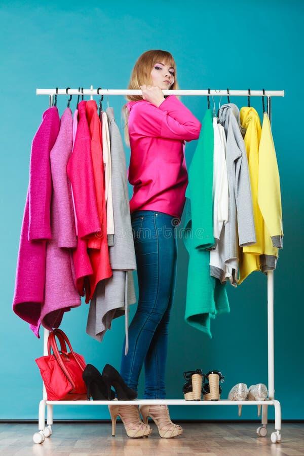 Vrouw die kleren in wandelgalerij of garderobe kiezen te dragen royalty-vrije stock fotografie