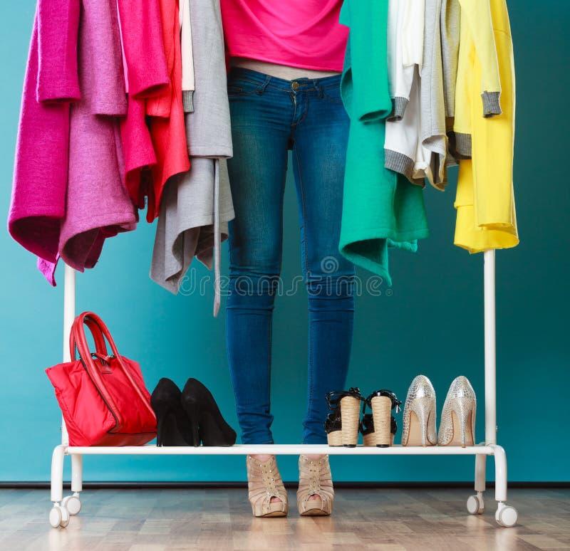 Vrouw die kleren in wandelgalerij of garderobe kiezen te dragen stock foto's