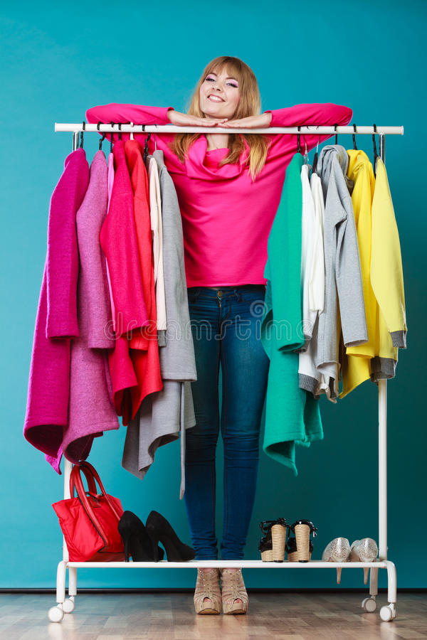 Vrouw die kleren in wandelgalerij of garderobe kiezen te dragen stock afbeelding
