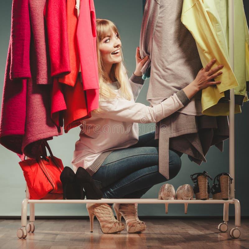 Vrouw die kleren in wandelgalerij of garderobe kiezen te dragen stock fotografie