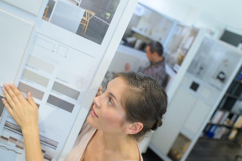 Vrouw die kleurenmonstertrekker bekijken in meubilairopslag stock fotografie