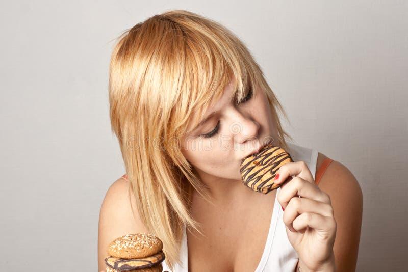 Vrouw die koekjes eten royalty-vrije stock afbeelding