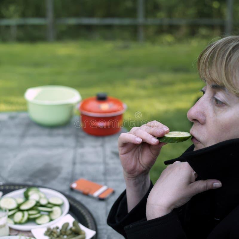 Vrouw die komkommer eet stock foto