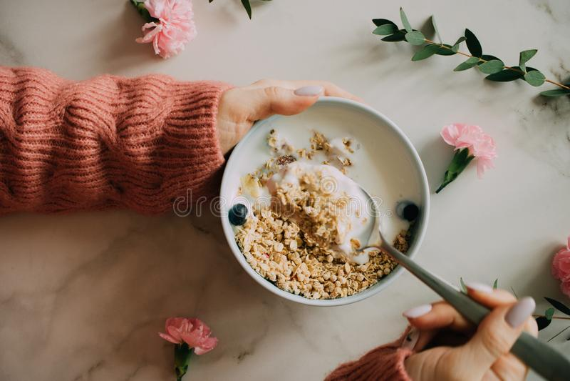 Vrouw die in koraal wollen sweater ontbijtkom eten stock fotografie