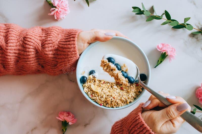 Vrouw die in koraal wollen sweater ontbijtkom met muesli en yoghurt, bessen en hazelnoten eten Het schone eten, vegetari?r, vegan stock foto's
