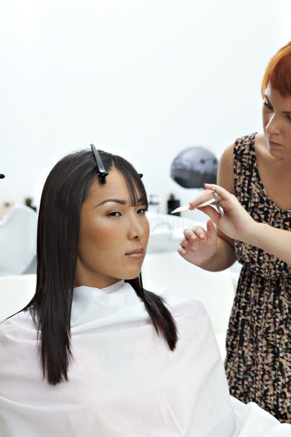 Vrouw die krijgen een nieuwe haarstijl bij schoonheidssalon stock afbeelding