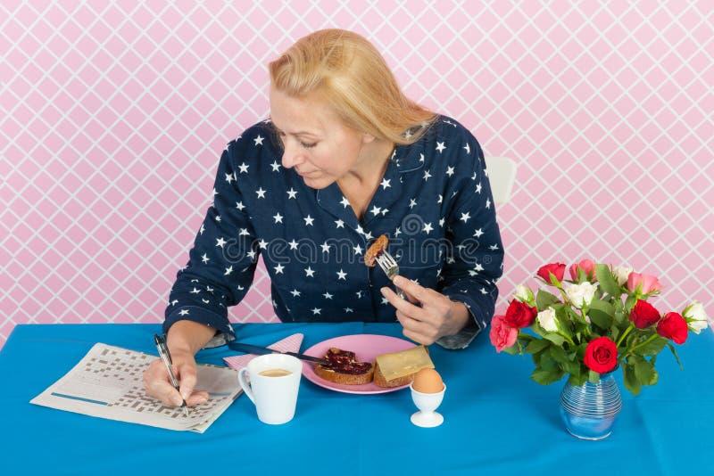 Vrouw die kruiswoordraadsel puzale in de ochtend maken stock afbeeldingen