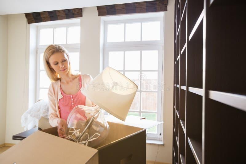 Vrouw die lamp verwijderen uit kartondoos bij nieuw huis royalty-vrije stock foto's