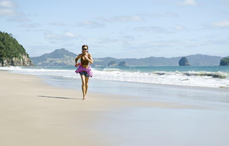 Vrouw die langs een mooi strand aanstoot. royalty-vrije stock afbeelding