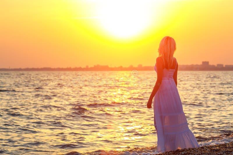Vrouw die langs het strand bij zonsondergang of zonsopganguren van rust lopen stock afbeelding