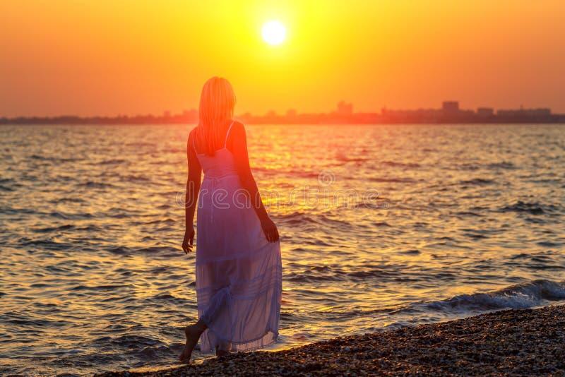 Vrouw die langs het strand bij zonsondergang of zonsopganguren van rust lopen stock foto's