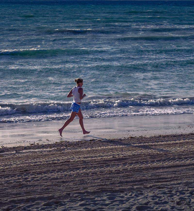 Vrouw die langs Strand lopen stock afbeeldingen