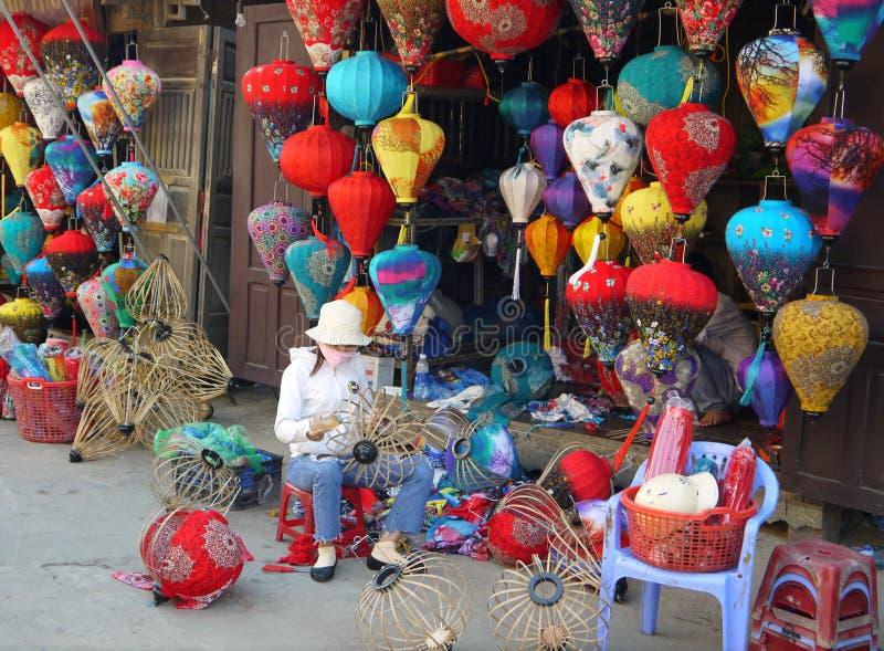 Vrouw die lantaarns voor hun winkel maken bij markt stock afbeelding