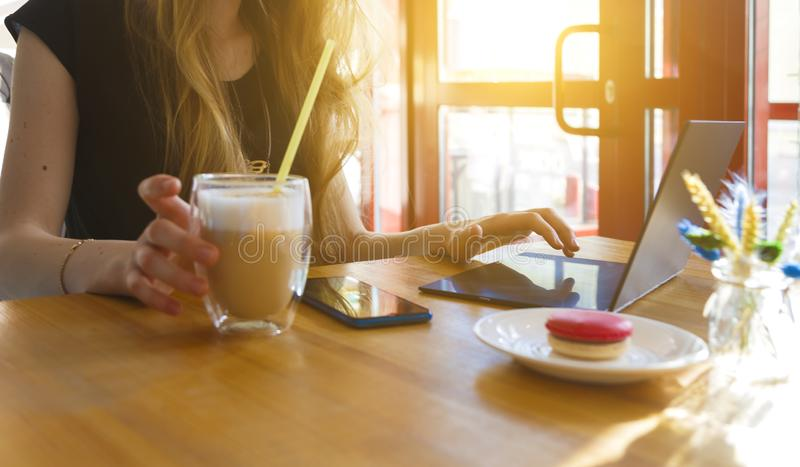 Vrouw die laptop met kop van koffie, glas van latte, de stralen van de zon van het venster met behulp van royalty-vrije stock fotografie