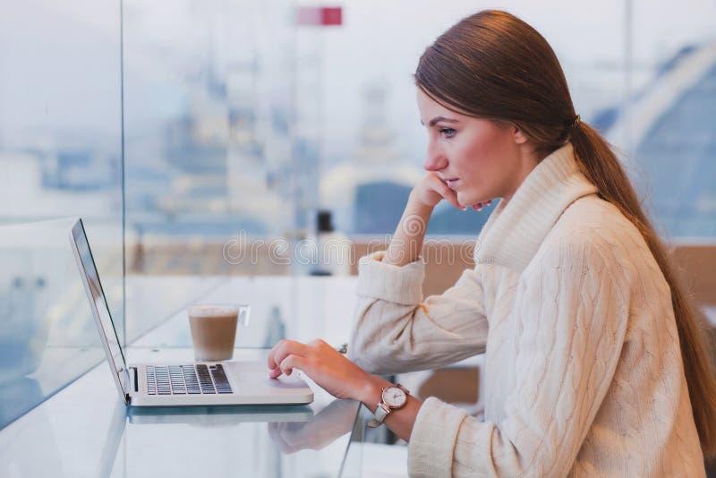 Vrouw die laptop in modern koffiebinnenland met behulp van royalty-vrije stock foto's