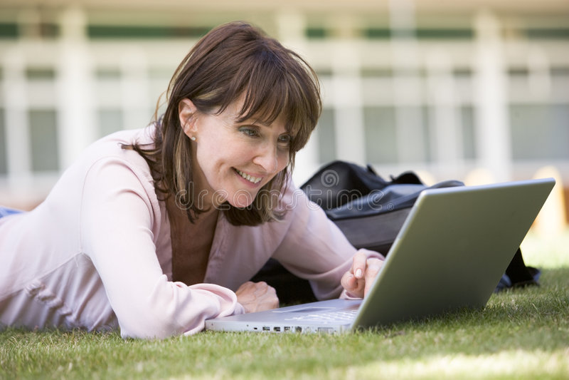 Vrouw die laptop op campus met behulp van stock foto