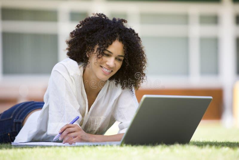 Vrouw die laptop op campus met behulp van royalty-vrije stock foto