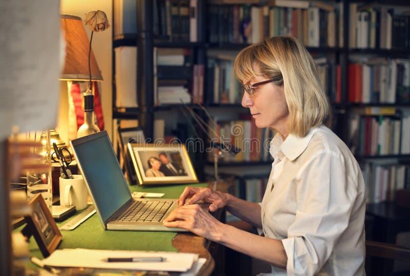 Vrouw die laptop op haar bureau met behulp van stock foto's