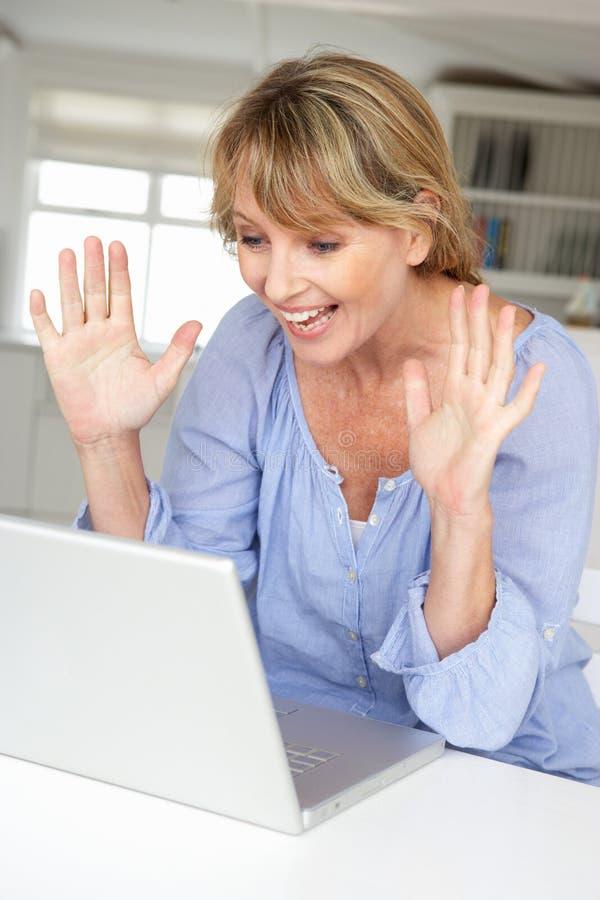 Vrouw die laptop op webcam met behulp van royalty-vrije stock afbeelding