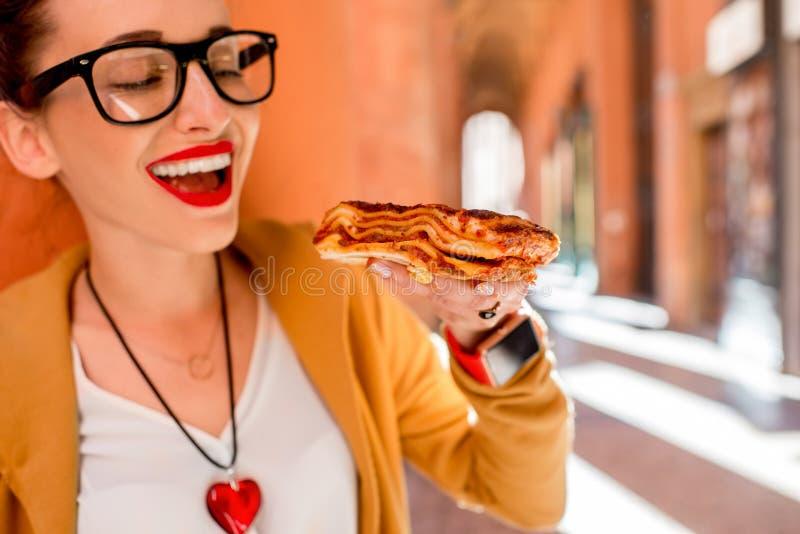 Vrouw die lasagna's in openlucht eten royalty-vrije stock afbeeldingen