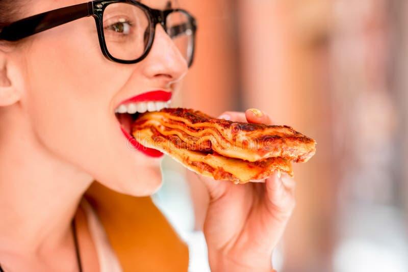 Vrouw die lasagna's in openlucht eten stock fotografie