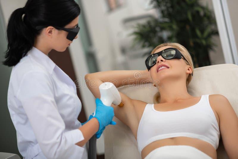 Vrouw die laserbehandeling voor haar oksels krijgt royalty-vrije stock fotografie