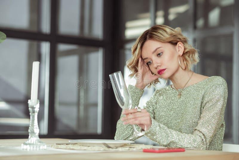 Vrouw die leeg glas bekijken die op echtgenoot van het werk wachten royalty-vrije stock foto's