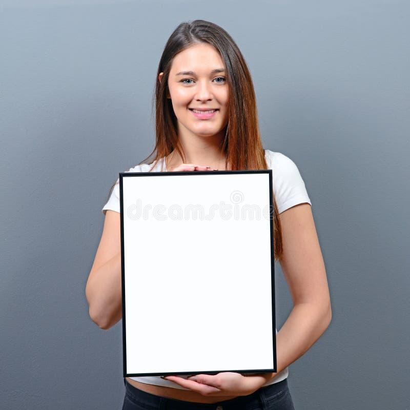 Vrouw die leeg kader met ruimte voor uw reclame houden tegen grijze achtergrond stock fotografie