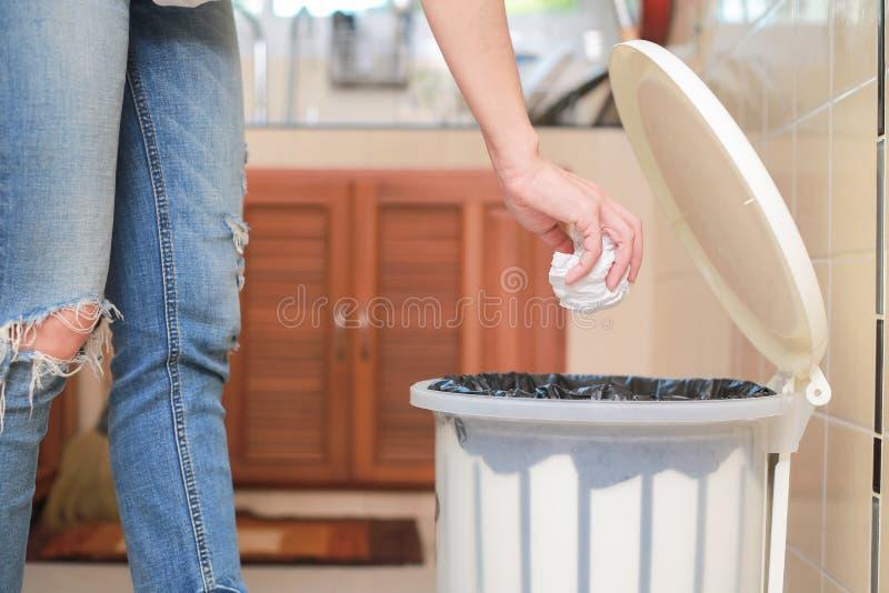 Vrouw die lege plastic zak in het recycling van bak in de keuken zetten stock foto's