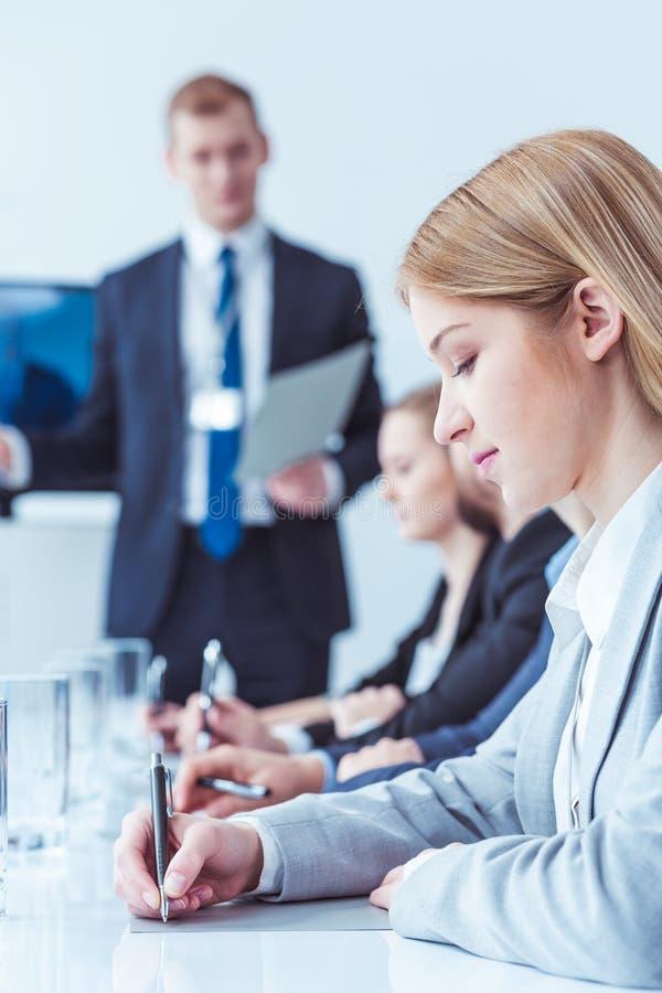 Vrouw die leiders` s richtlijnen neerschrijven stock fotografie
