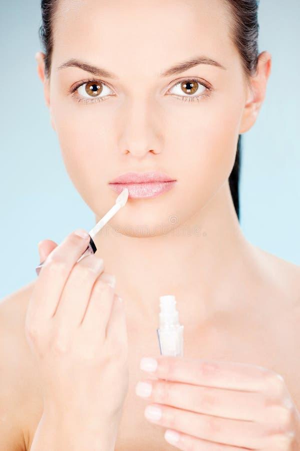 Vrouw die lippenstift op haar lippen zetten royalty-vrije stock afbeeldingen