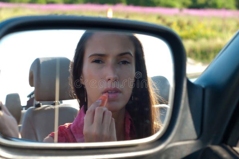 Vrouw die lippenstift toepassen die autospiegel bekijken stock afbeeldingen
