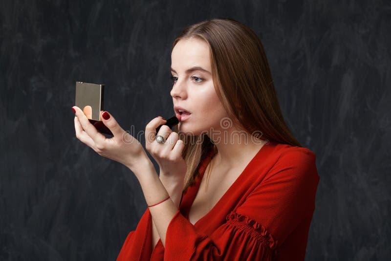 Vrouw die lippenstift toepassen die binnen op de spiegel eruit zien stock foto's