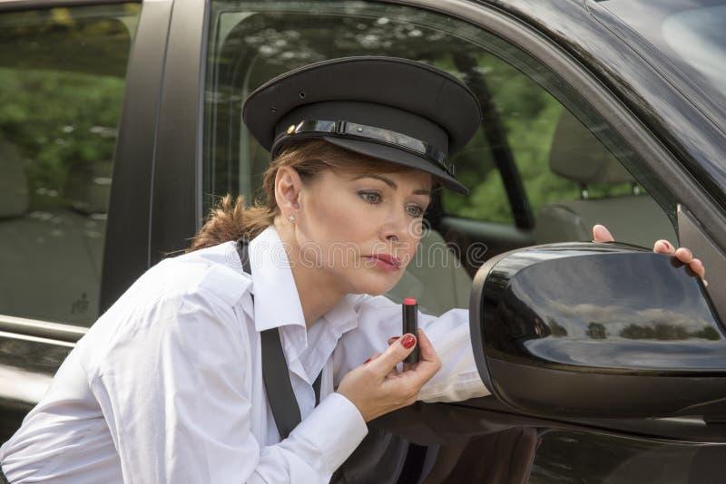 Vrouw die lippenstift toepassen die in de spiegel van de autovleugel kijken royalty-vrije stock afbeeldingen