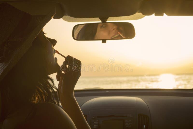 Vrouw die lippenstift toepassen en achteruitkijkspiegel in auto met behulp van bij de zonsondergang stock foto's