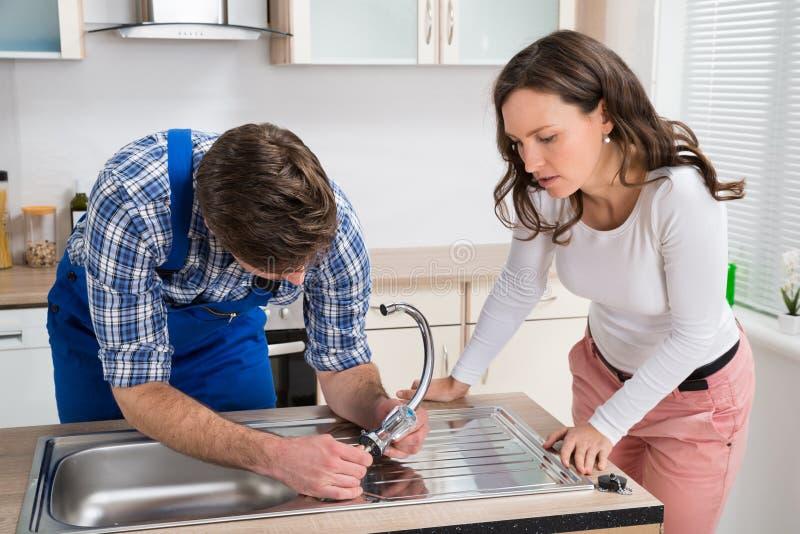 Vrouw die Loodgieter Fixing Steel Tap bekijken stock foto