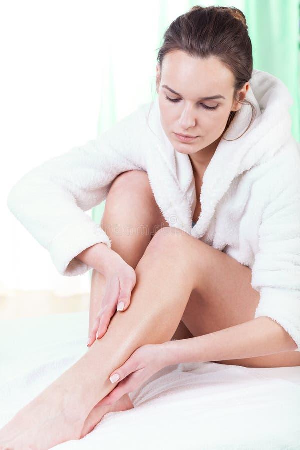 Vrouw die lotion op haar benen wrijven stock afbeelding