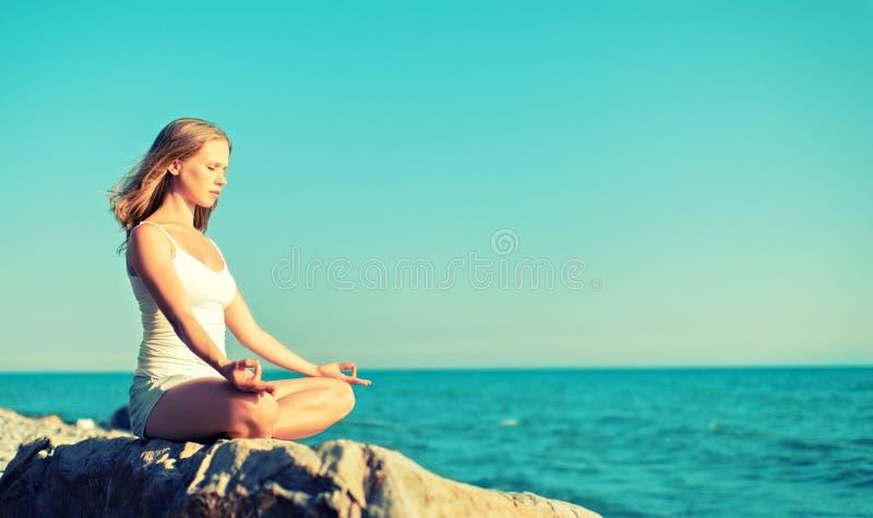 Vrouw die in lotusbloemyoga mediteren op strand royalty-vrije stock fotografie