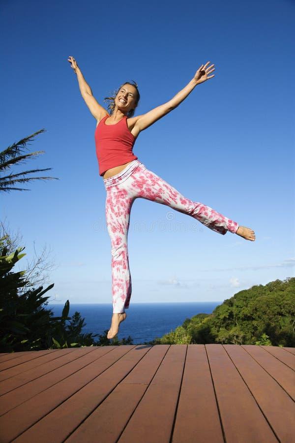 Vrouw die in lucht springt. stock fotografie