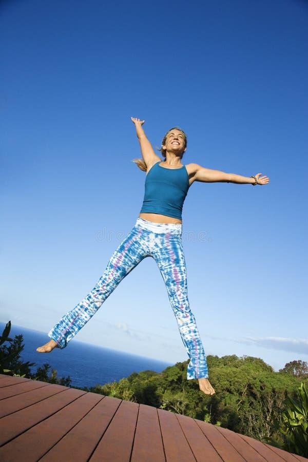 Vrouw die in lucht springt. stock foto's