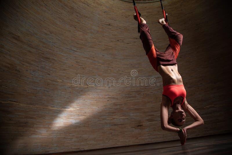 Vrouw die luchtyoga met haar benen in de riemen oefent stock afbeeldingen