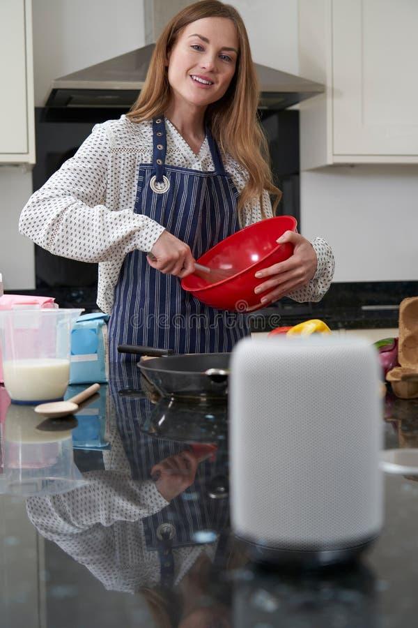 Vrouw die Maaltijd voorbereiden die thuis Digitale Hulpvraag stellen stock afbeelding