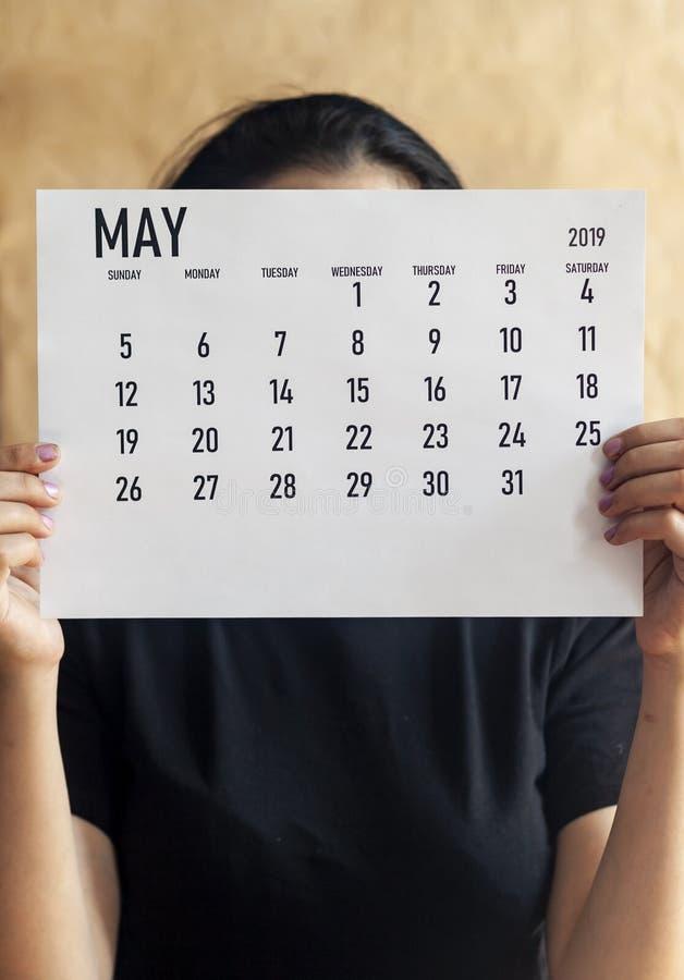 Vrouw die Maandelijkse kalender van Mei, 2019 houden royalty-vrije stock afbeeldingen