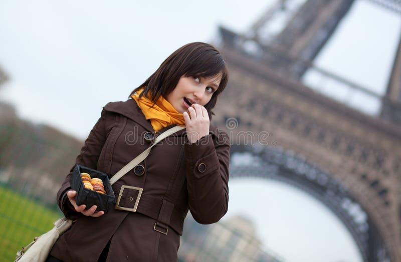 Vrouw die makarons eet dichtbij de Toren van Eiffel royalty-vrije stock afbeeldingen