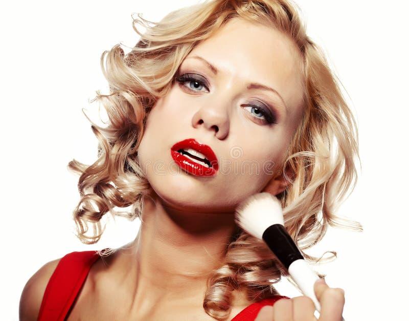 vrouw die make-up op haar gezicht toepast stock afbeeldingen