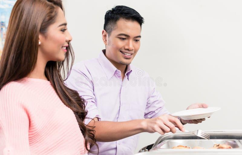 Vrouw die man dienend buffetvoedsel bekijken stock foto