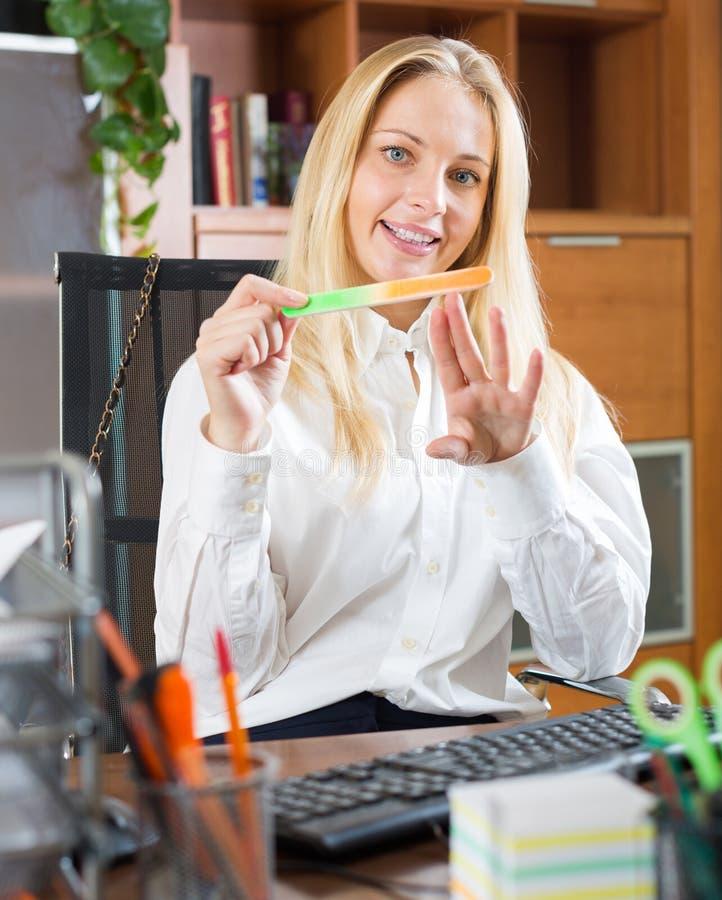 Vrouw die manicure doen op kantoor stock foto's