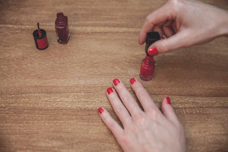 Vrouw die Manicure doen die Rood Nagellak toepassen Op houten lijst Ondiepe diepte van gebied royalty-vrije stock foto's